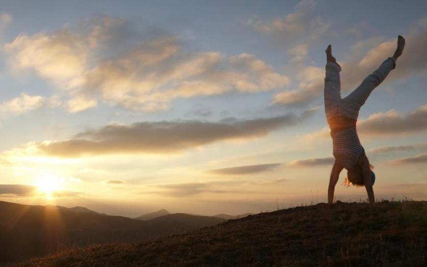 Acrobatic girl on grassland of sunrise